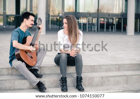 Guy making guitar music to a beautiful young girl outdoors #1074150077