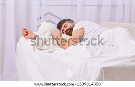 Guy on calm face sleeping on white sheets, pillow. Nap and siesta concept. Man laying on bed, covered with blanket, white curtains on background. Macho with beard sleeping, relaxing, having nap, rest. #1309814350