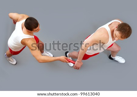 Guy passing the baton to his team member in the rush of a relay race