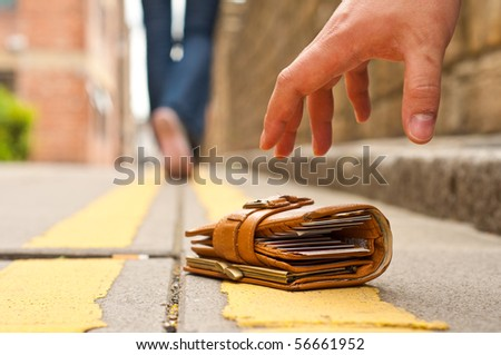 guy picking up a lost purce/wallet