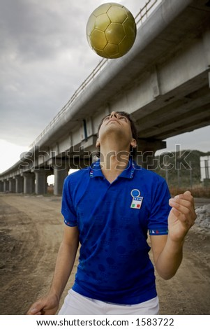 guy playing football under a bridge