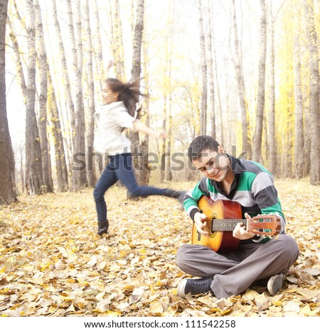 guy playing on guitar and the girl is dancing