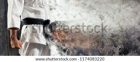 Guy poses in white kimono with black belt.  Japanese judo banner Foto stock ©