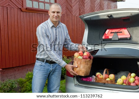 Guy puts apples harvest in the trunk of car