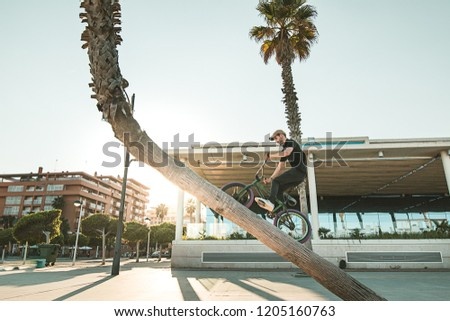 Guy riding and jumping with a bmx bike. BMX rider doing freestyle on the street
