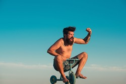 Guy riding childs tricycle. Portrait of a bearded man as a crazy hipster having fun with bicycle outdoors. Excited young male riding a small bicycle and gesturing happiness