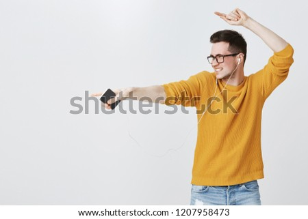 Guy rocking dance-floor as listening music in earphones, dancing and pointing left at copy space feeling enthusiastic and upbeat of enjoying cool songs in earbuds, holding smartphone, wearing sweater