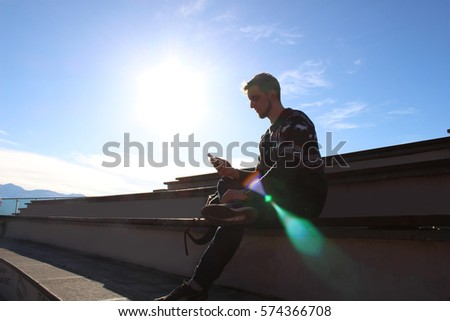 guy sits on stairs with smartphone sunny weather  #574366708