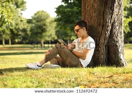 guy sitting beneath the tree using tablet - stock photo