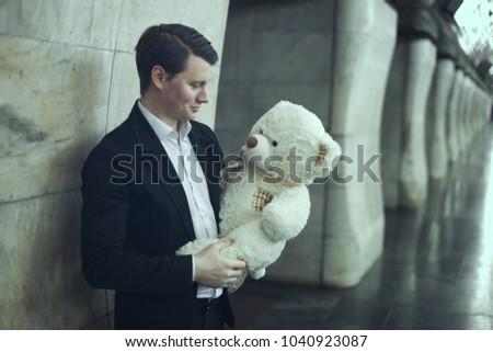 Guy smiles a big plush toy. Childish mood concept.