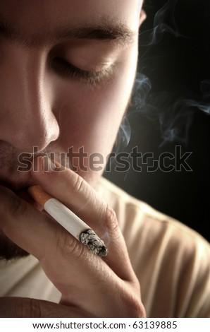 guy smoking cigarette on dark background