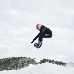 Guy snowboarder jumping in the air. Man making jump with snowboard while sliding down snowy hill in winter mountains. Concept of winter sport activities.