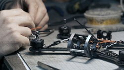 Guy soldering drone FPV wires. Frontframe view