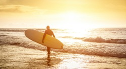 Guy surfer walking with surfboard at sunset in Tenerife - Surf long board training practitioner in action - Sport travel concept with soft focus water near feet - Warm sunshine color filtered tones