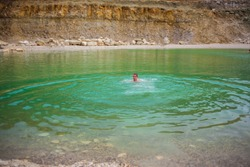 Guy swimming in the canyon lake with emerald-colored clear water. Man swims in a basin with water saturated with green color. Summer water activities.