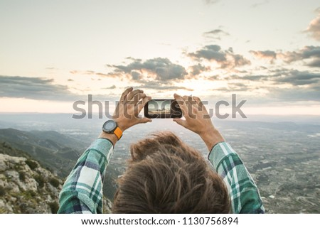 Guy taking a picture with the mobile phone to a valley.Man taking a picture on the mountain