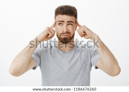 Guy trying focus, think up new plan. Determined, thoughtful handsome charismatic man with beard and blue eyes squinting, smirking holding fingers on temples focusing on importrant game, concentrating #1186676260