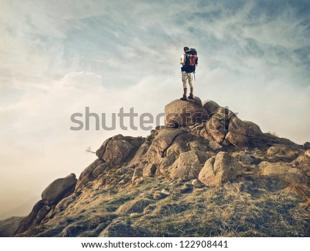 Guy with a travel backpack on the top of a boulder