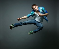 Guy with a wide smile jumping sideward and looking at camera