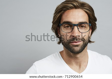 Guy with beard and glasses in grey studio, portrait - Shutterstock ID 712900654