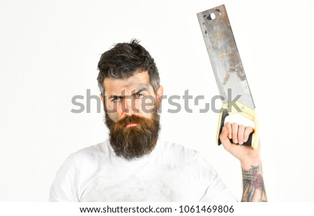 Guy with beard covered with dust. Builder, worker, carpenter, handyman holds saw or hacksaw, white background.