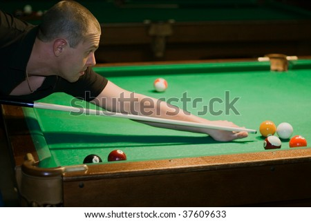 Guy with cue for the billiard table aiming to ball