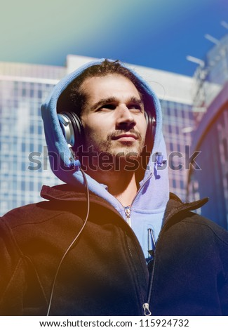 Guy with headphones walking around the city and listening to music