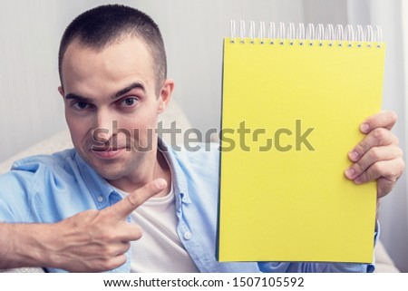 Guy with notebook, guy points the finger at the notepad, sitting on sofa at home, copy space, toned