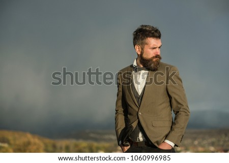 Guy with strict face enjoys scenery and view. Hipster with stylish appearance in front of dramatic sky, skyline. Man with beard and mustache on top of mountain, scenery on background. On top concept. #1060996985