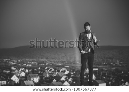 Guy with strict face in suit feels free and successful. Hipster with stylish appearance in front of sky with rainbow. Successful stylish man with scenery on background. Success and freedom concept. #1307567377