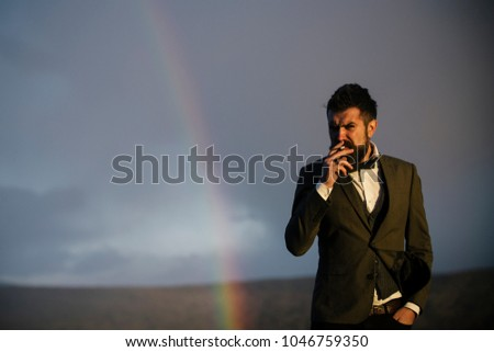 Guy with strict face in suit feels free and successful. Hipster with stylish appearance smoking in front of sky with rainbow. Success and freedom concept. Successful man with scenery on background. #1046759350