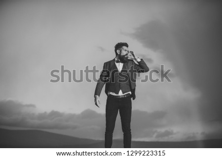 Guy with strict face in suit feels free and successful. Hipster with stylish appearance smoking in front of dramatic sky with rainbow. Lord of world concept. Successful man with scenery on background. #1299223315