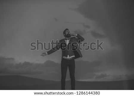 Guy with strict face in suit feels free and successful. Lord of world concept. Successful man with scenery on background. Hipster with stylish appearance smoking in front of dramatic sky with rainbow. #1286144380