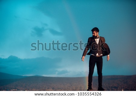 Guy with strict face in suit feels free and successful. Successful man with scenery on background. Hipster with stylish appearance smoking in front of sky with rainbow. Success and freedom concept. #1035554326