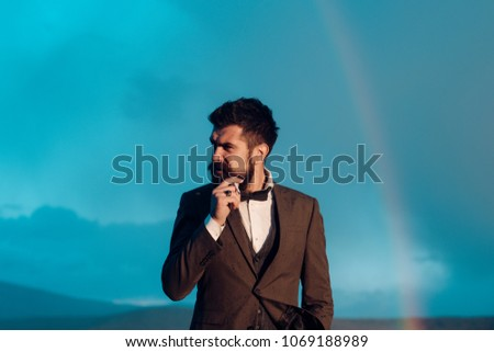 Guy with strict face in suit feels free and successful. Successful man with scenery on background. Hipster with stylish appearance smoking in front of sky with rainbow. Success and freedom concept. #1069188989