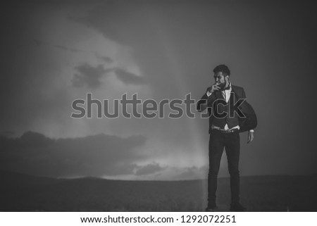 Guy with strict face in suit feels free and successful. Successful man with scenery on background. Hipster with stylish appearance smoking in front of sky with rainbow. Success and freedom concept. #1292072251