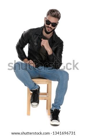 guy with sunglasses, black jacket and blue jeans sitting on chair with his elbow on leg on white background