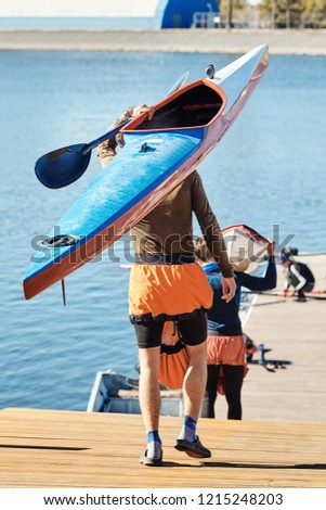 Guys carry kayaks for sports. Summer water sports. Travel kayaking, leisure leisure, sporting events. #1215248203