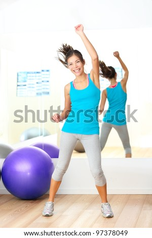 Gym aerobics fitness dance instructor. Woman dancing happy in fitness center. Young beautiful mixed race Caucasian / Chinese Asian female fitness model. - stock photo