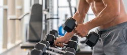 gym and fitness background banner of close up dumbbell with hand of athletic bodybuilder man lifting from dumbbell rack in gym and fitness club