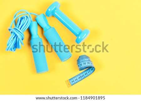 Gym and healthy lifestyle tools. Weight loss and sports concept. Dumbbell, twisted measuting tape and jumping rope lay top on yellow background. Centimeter in blue color near colorful sport equipment. #1184901895