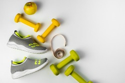 Gym and workout,  sports shoes, sneakers, Healthy lifestyle concept foto. Flat lay of sport. Athlete's set with centimeter tape, green apple and dumbbells on a grey background