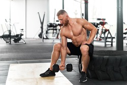 Gym athlete bicep exercise dumbbell muscular man sit wheel holding lift barbell. Functional cross training indoor. Handsome caucasian bearded guy do workout with dumbbell.