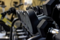 Gym background Fitness equipment dumbbells weight for a workout. Background image of dumbbells in row on equipment stand in modern gym. Dumbbells on the racks at the gym,exercise and relaxing concept.