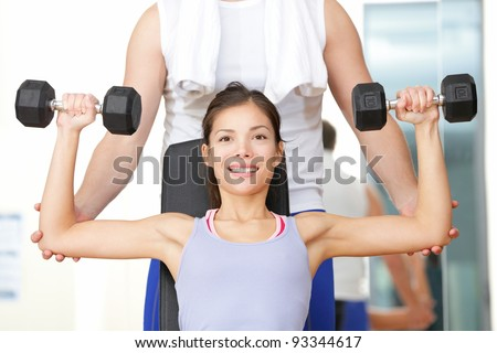 Gym fitness people - woman lifting weights with help from instructor and fitness trainer in gym. Beautiful smiling happy fit female fitness model training shoulders.