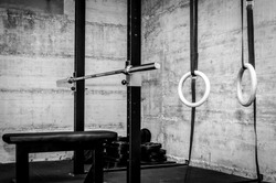 Gym interior closeup of benchpress  bench gymnastics rings and barbell plate weights on the floor in the corner hard core black and white dark image