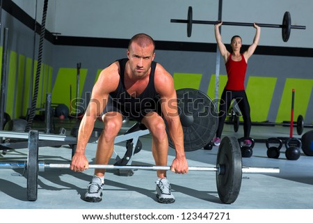 gym man and woman with weight lifting bar workout in exercise