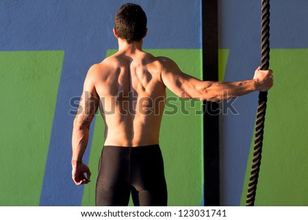 gym man holding hand a climbing rope rear view