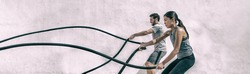 Gym people training battle rope exercise panorama. Fitness gym fit couple exercising with battling ropes. Woman and man training together working out arms and cardio for cross fit exercises workout.
