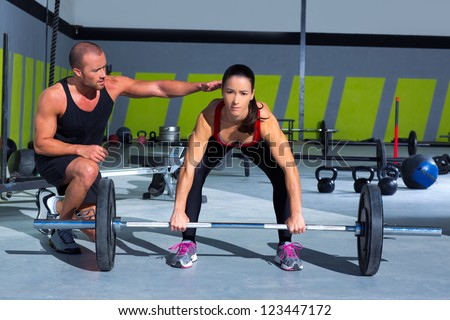 gym personal trainer man with weight lifting bar woman workout in fitness exercise